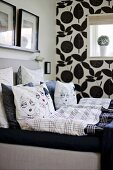 Scatter cushions with comic-style covers on bed; black and white floral wallpaper on one wall in background