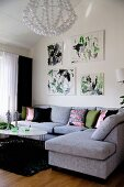 Modern, pale grey corner sofa in living room below drawings on wall