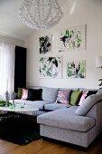 Modern, pale grey corner sofa in living room below drawings on wall