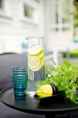Glass carafe of lemon water, blue drinking glasses and pot of herbs on black side table