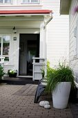 Ornamental grass in white planter on terrace in front of white clapboard house with porch and open door