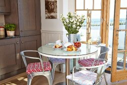 Classic, metal chairs and round table in front of open terrace doors in corner of dining room