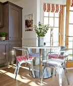 Classic, metal chairs and round table in front of open terrace door with red and white striped Roman blinds on windows