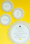 Letters stuck on flat magnets on round metal panels with lace edging used as noteboards