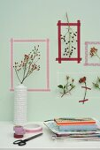Picture frames of washi tape around sprigs of rose hips on wall