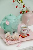 Turquoise teapot, vintage cup, halved rose hips and fabric teabags on pink serving tray