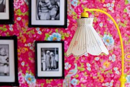 Standard lamp with nostalgic lampshade in front of framed black and white photos on floral wallpaper