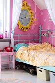 Child's bed with turquoise, retro metal frame below clock with yellow, ornate frame on pink wallpaper