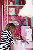 Young girl working at desk in child's bedroom decorated in nostalgic style