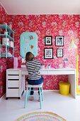 Girl sitting at desk in nostalgic bedroom; pink wallpaper with floral pattern