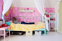 Young girl on canopied bed with draped, white curtains against pink wallpaper with ornamental pattern