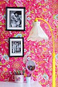 Standard lamp with nostalgic fabric lampshade and yellow-painted base, framed photos on pink wallpaper with floral pattern