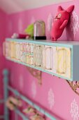Cabinet with retro glass scoops mounted on wall with pink wallpaper