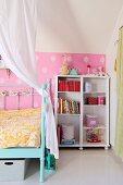 White wooden shelves next to metal lattice bed in nostalgic bedroom