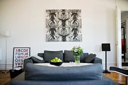 Black and white, graphic artwork on wall behind grey sofa set