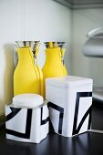 Storage jars with black and white graphic patterns and thermos flasks in yellow neoprene cosies