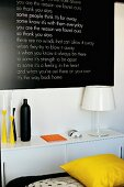 White table lamp and colourful candlesticks on sideboard below black panel with white lettering on wall