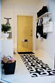 Black and white patterned runner on white hallway floor, wall-mounted coat rack and front door painted pale yellow with letterbox cage