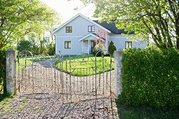 Wrought iron gate leading to garden and pale grey, clapboard country house