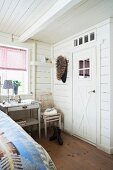 Corner of white, wood-clad bedroom