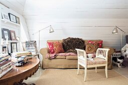 White, rustic wooden stool with armrests in front of sofa in pleasant attic room