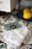 Linen cloth on patterned tiled surface