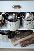 Zinc pots on open-fronted shelves