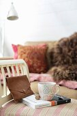 Coffee cup on book and leather clutch bag on stool with arm rest