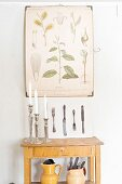Candlesticks on simple console table below botanical illustrations on plate