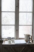 Jug and glasses on tray table below window with view into snowy garden