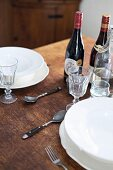 White pace settings and wine bottles on rustic wooden table