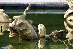 Metal dragon figures in a pond in the Garden of the Palace of Versailles