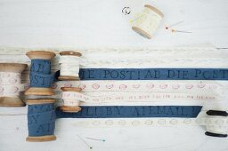 Hand-printed, blue and white fabric ribbons wound on vintage wooden reels