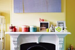 Storage jars on white mantelpiece against wall painted pale yellow