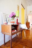 Simple wooden console table with bouquet and table lamp next to Bauhaus shell chair on wooden floor in hallway