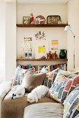 Two white dogs and many scatter cushions with graphic patterns on corner sofa in front of bookshelves in niche