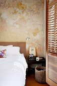 Bed with white bed linen, bedside table and laundry basket in front of wall with vintage patina