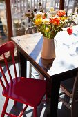 Poppies of various colours in china jug in sunshine on vintage table with red-painted kitchen chair to one side