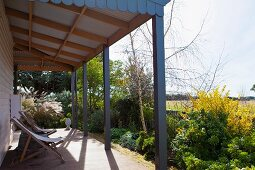 Wooden deckchairs on roofed terrace with wide view across summery garden in rural setting