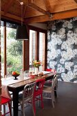 Red and white chairs at rustic wooden table in front of wall covered in floral wallpaper