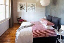 Double bed with red and white striped bed linen against grey wall and white wooden wall in background in rustic, modern bedroom
