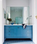 Fitted washstand with blue base cabinets below mirrored wall in rustic bathroom