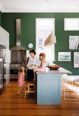 Mother and children in open-plan kitchen with little girl sitting on counter and stainless steel cooker against dark green wall in background