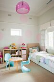 Pale blue plastic shell chairs at round wooden table and bed in corner below pastel circles on wall in child's bedroom