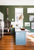 Kitchen counter painted grey-blue on wooden floor in warm shade and stainless steel cooker against dark green wall in open-plan interior