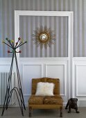 Fur cushion on brown easy chair and retro coat stand against wall with striped wallpaper above wood-panelled dado