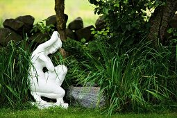White statue of woman amongst grasses and low stone wall in summer garden