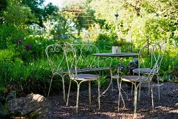 Idyllic, vintage seating area with metal bistro table and chairs on gravel floor in garden