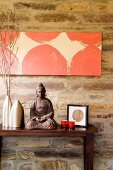Buddha figurine flanked by metal vases and tealight holders on dark wooden table below modern artwork on stone wall