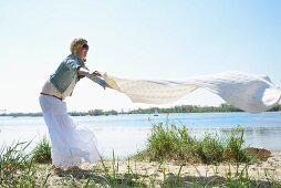 Frau breitet eine Picknickdecke am Strand aus